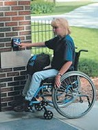 lady in wheelchair using access control equipment. Assessability specialises in assessing disability access requirements.